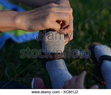 Close-Up Of Hands Helping Kid With Footwear - Stock Photo