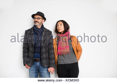 Persian man and Tibetan woman holding hands and leaning against a wall, man looking away while woman is looking at man; Toronto, Ontario, Canada - Stock Photo