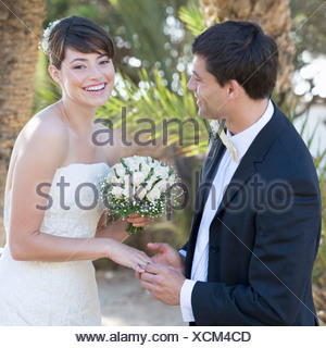 A groom placing the ring on his bride - Stock Photo