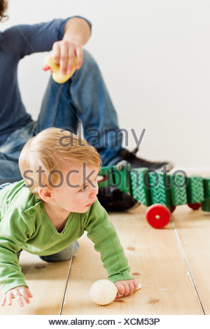 Studio shot of father and baby daughter playing on floor - Stock Photo