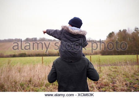 Father Gives Son Ride On Shoulders During Countryside Walk - Stock Photo