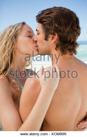 Young couple standing on the beach while kissing each other - Stock Photo