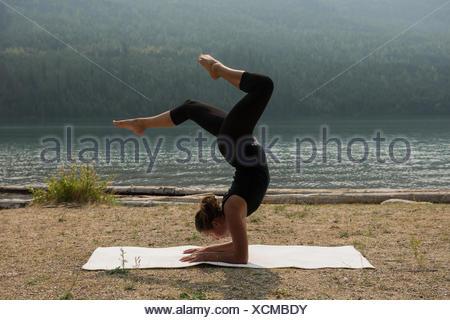 Fit woman doing acrobatic yoga near the sea coast - Stock Photo