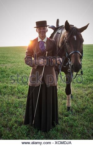 Portrait of woman standing with dressage horse in field - Stock Photo