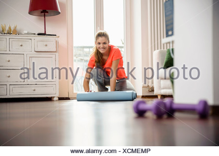 Young woman rolling up exercise mat at home - Stock Photo
