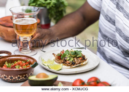 A slow cooked beef brisket chili taco served to a person in a picnic table with beer. - Stock Photo