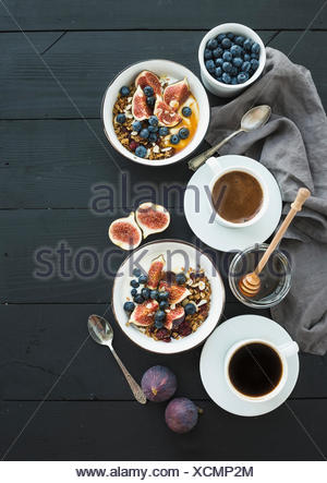 Healthy breakfast set. Bowls of oat granola with yogurt, fresh blueberries and figs, coffee, honey, over black wooden backdrop. - Stock Photo