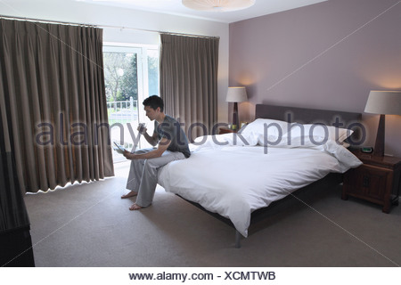Man sitting on bed looking at digital tablet - Stock Photo
