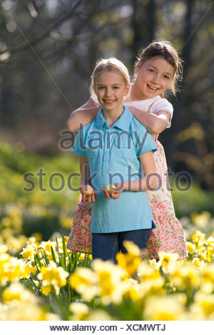 Two young girls holding decorated Easter eggs in field of daffodils - Stock Photo