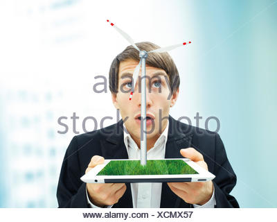 Businessman with a surprised face holding an iPad with a wind turbine, symbolic image for sustainable energy - Stock Photo