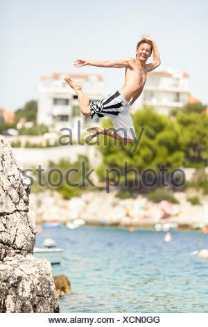 Teenage boy jumping out of rock - Stock Photo