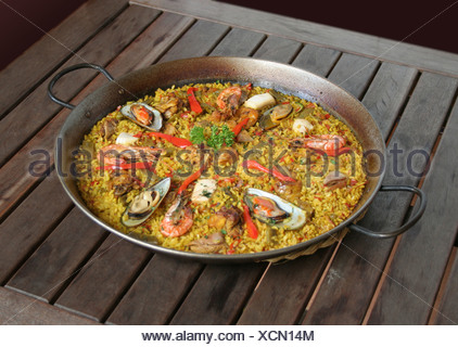 Spanish Paella (rice pan) with seafood on a wooden table Stock Photo