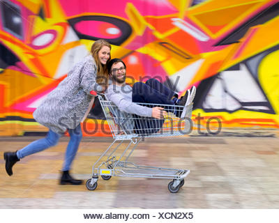 Young woman pushing man in shopping cart, laughing and running - Stock Photo