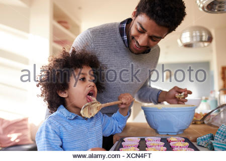 Father Baking Cake With Son In Kitchen At Home - Stock Photo