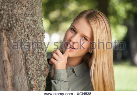 Germany, Duesseldorf, young woman playing hide and seek - Stock Photo