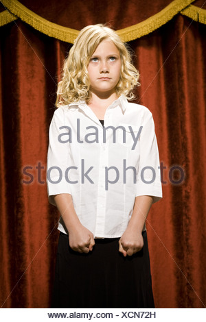 Girl standing on stage with lips pressed together - Stock Photo
