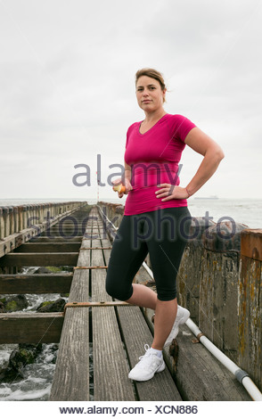 Woman standing on pier wearing sports clothing - Stock Photo