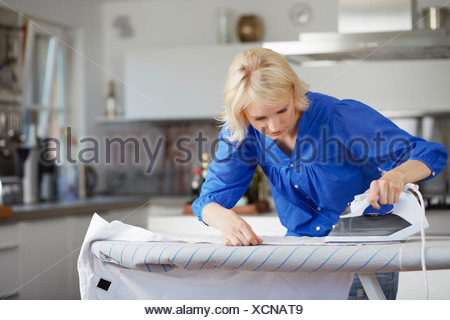 Woman carefully ironing husband's shirt - Stock Photo