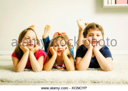 Three children relaxing hand on chin, Munich, Bavaria, Germany - Stock Photo