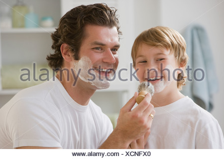 Father putting shaving cream on son's face - Stock Photo
