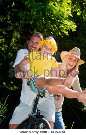 Austria, Salzburg County, Family sitting on old bicycle - Stock Photo