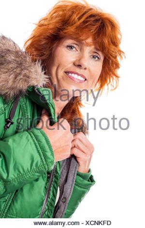 erwachsene rothaarige lachende frau mit warmer grüner jacke mit kapuze isoliert - Stock Photo