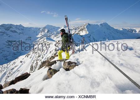 Freeride skier standing on the ridge, Winterklettersteig climbing route, Arlberg, Verwall Group, North Tyrol, Austria - Stock Photo