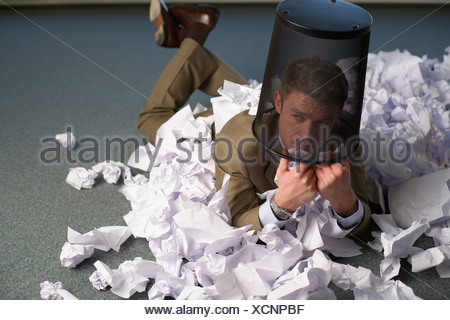 Businessman wearing a trash on head lying between crushed paper on floor - Stock Photo