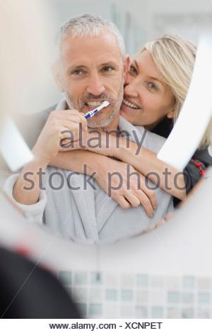 Man brushing his teeth with wife - Stock Photo