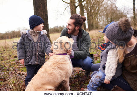 Family With Dog On Winter Walk Playing In Countryside - Stock Photo