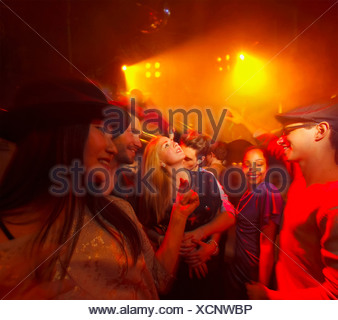 Group of people at party, man kissing woman's neck - Stock Photo