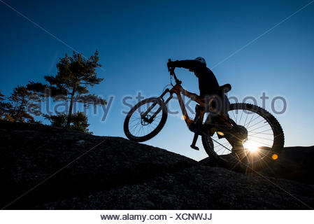 Silhouette Of Alex Leich With Mountain Bike On The Bare Granite Slabs In North Conway, New Hampshire - Stock Photo