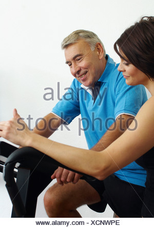 Woman and man in gym on exercise machines - Stock Photo