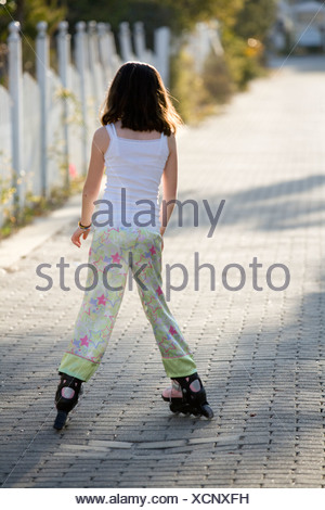 A young girl is roller blading down an alley with a picket fence in the background. - Stock Photo