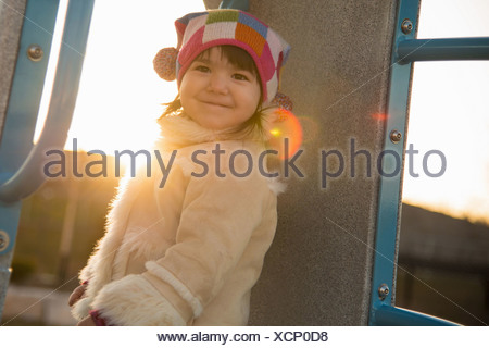 Portrait of young girl in sheepskin coat in playground - Stock Photo