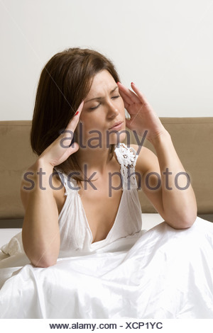 Woman rubbing temples in bed - Stock Photo