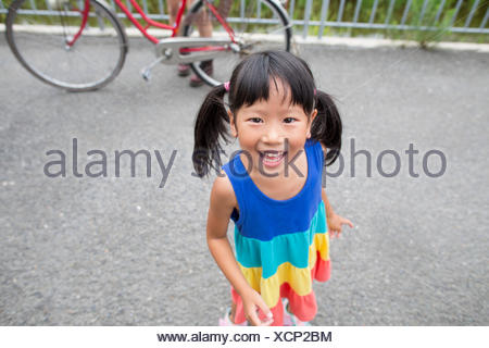 A young girl with pigtails smiling at the camera. - Stock Photo
