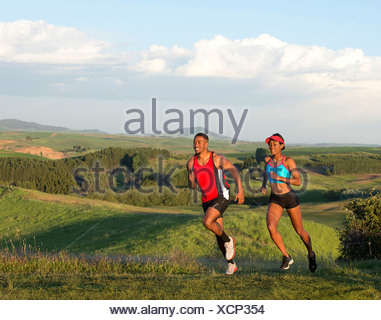Young couple jogging in landscape, Othello, Washington, USA - Stock Photo