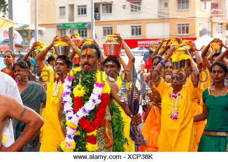 Holy man and pilgrims making milk sacrifice, Hindu festival Thaipusam, Batu Caves limestone caves and temples, Kuala Lumpur - Stock Photo