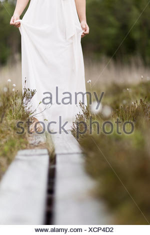 Sweden, Vastmanland, Teenage girl (16-17) in white dress standing on overpass in meadow - Stock Photo