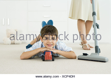 Little boy lying on the ground with toys, smiling at camera, mother vacuuming around him - Stock Photo