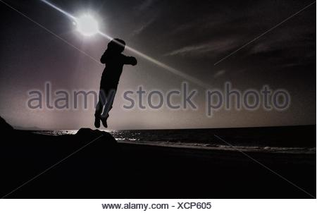 Person Leaping Into Air Against Sun - Stock Photo