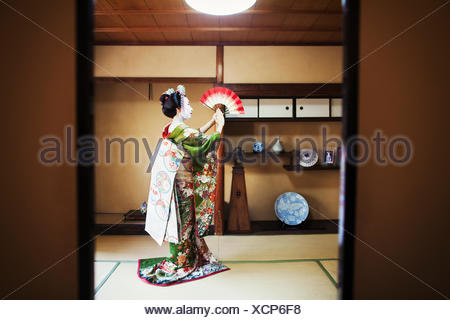 A woman dressed in the traditional geisha style, holding an open fan up, her kimono arranged on the floor. - Stock Photo