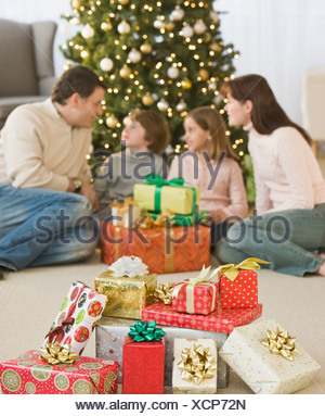 Family with gifts in front of Christmas tree - Stock Photo