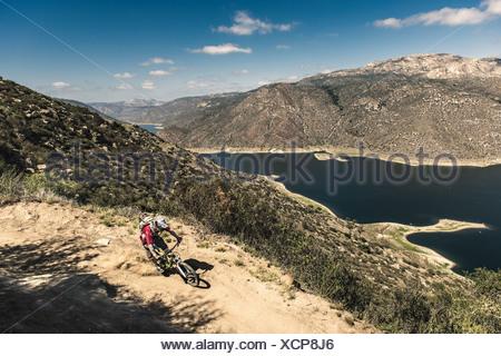 Downhill mountain biker riding downhill - Stock Photo