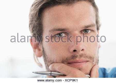 Portrait of mid-adult businessman with pen - Stock Photo