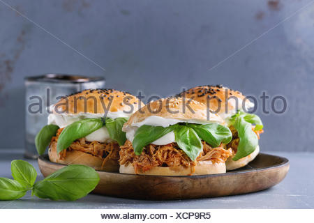 Homemade mini burgers with pulled chicken, basil, mozzarella cheese and yogurt sauce on wooden plate over gray texture background. Healthy fast food c - Stock Photo