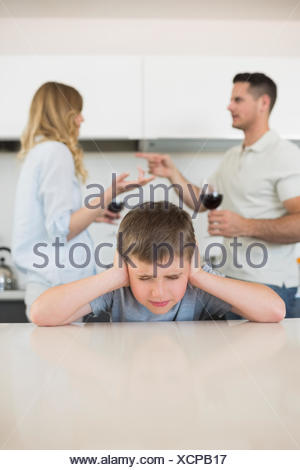 Irritated boy covering ears while parents arguing - Stock Photo