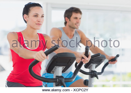 Determined couple working out at spinning class in gym - Stock Photo