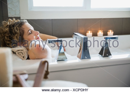 Mature woman with eyes closed relaxing in bathtub - Stock Photo
